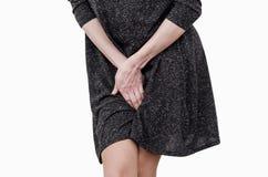 Nik?a dziewczyna w ciemnej sukni do?wiadcza niewygod? w macicie, b?l, r?ki mi?dzy jej nogami Incontinence, potrzeba siusia? w obraz stock