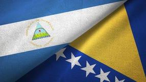 Nikaragua, Bośnia i Herzegovina dwa flagi tekstylny płótno, tkaniny tekstura obrazy royalty free
