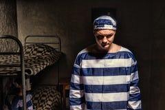 Nikczemny męski więzień jest ubranym więzienia jednolitego trwanie pobliskiego łóżko w Obraz Stock