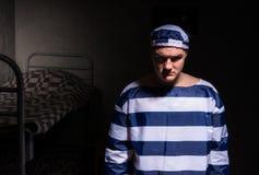 Nikczemny męski więzień jest ubranym więzienie jednolitą pozycję w małym Obraz Stock