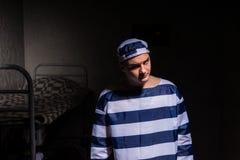 Nikczemny więzień jest ubranym więzienie jednolitą pozycję w małym zmroku Zdjęcia Stock