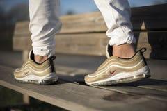 Nike Air Max 97 Gouden schoenen in de straat Stock Fotografie