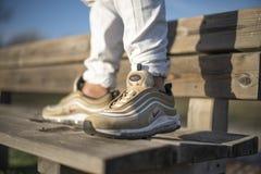 Nike Air Max 97 Gouden schoenen in de straat Stock Foto
