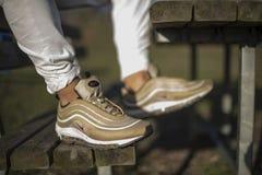 Nike Air Max 97 Gouden schoenen in de straat Royalty-vrije Stock Foto