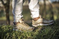 Nike Air Max 97 guld- skor i gatan Fotografering för Bildbyråer