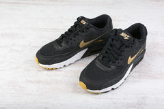 Nike Air MAX women`s shoes - sneakers in black, on white wooden background. Stock Photography