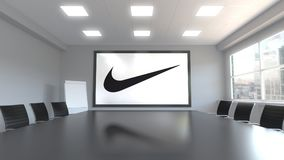 Nike inscription and logo on the screen in a meeting room. Editorial 3D rendering