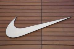 Nike logo med en träbakgrund Arkivfoto
