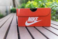 Nike röd ask , Asknikeskor på asfaltvägen i parkera Med kopiera utrymme för text arkivfoton
