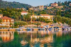 Nikiana beach, Lefkada island of Greece. Traditional Greek architecture and boats illuminated by sunrise light on Nikiana beach, Lefkada island of Greece stock image