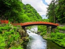 NIKKO, ΙΑΠΩΝΊΑ - 14 ΑΥΓΟΎΣΤΟΥ 2017: Κόκκινη αρχαία γέφυρα, η γέφυρα Shinkyo πέρα από τον ποταμό Daiwa μια νεφελώδη ημέρα, κόσμος Στοκ Εικόνες