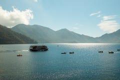 Nikko Japão - 3 de outubro de 2015: Os barcos dos homens do navio e da pesca do turista estão no lago ChuzenjiChuzenjiko fotografia de stock royalty free