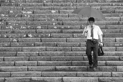 Nikko, Japan; August 1 2017. Nikko, Japan August 1 2017: A man with umbrella going down the stairs Royalty Free Stock Images