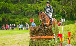 Niklas Bschorer riding for Germany at Blair. Niklas Bschorer riding Ballyengland Rebel in the cross country competition  for Germany jumps the hedge at Blair Royalty Free Stock Images