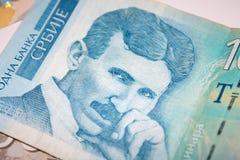 Nikola Tesla cuenta de 100 dinares en la pila de cuentas servias de los dinares Imagen de archivo