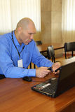 Nikolay Valuev sits at table and looks at phone Royalty Free Stock Images