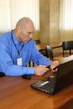 Nikolay Valuev sitzt am Tisch und betrachtet Telefon Lizenzfreie Stockbilder