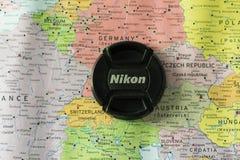 Nikon around Europe. Nikon lens cap on background of Europe map Stock Images