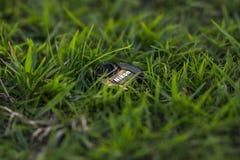 Nikon art. Nikon lens cap in grass, green it, green technology royalty free stock images