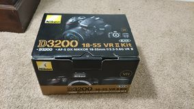 Nikon Camera Box. Nikon camera kit with a D3200 body, two lenses, a bag and case, batteries, SD cards, manual and accessories. New photographer equipment stock photo