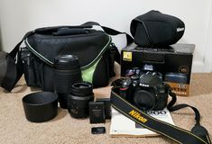 Nikon Camera Gear. Nikon camera kit with a D3200 body, two lenses, a bag and case, batteries, SD cards, manual and accessories. New photographer equipment stock photo
