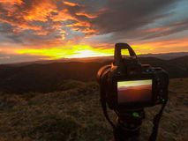 Nikon camera taking a photo of a sunrise. Sunrise in the North of Spain stock photography