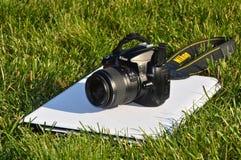 Nikon D5000 body digital SLR camera and laptop. Nikon D5000 body digital SLR camera 18-55 mm lens and white laptop, on the grass stock photography