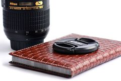 Nikon lens cap on leather notebook Royalty Free Stock Image