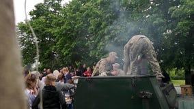 NIKOPOL, DE OEKRAÏNE - MEI, 9, 2019: De havermoutpap van Oekraïense militaire koksmilitairen en traktatiesmensen aan het bij de p stock videobeelden