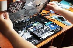 NIKOPOL, UCRÂNIA - EM JUNHO DE 2018: A posse do técnico a chave de fenda para reparar o computador, o conceito do material inform foto de stock