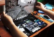 NIKOPOL, UCRÂNIA - EM JUNHO DE 2018: A posse do técnico a chave de fenda para reparar o computador, o conceito do material inform fotografia de stock