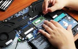 NIKOPOL, UCRÂNIA - EM JUNHO DE 2018: A posse do técnico a chave de fenda para reparar o computador, o conceito do material inform imagem de stock