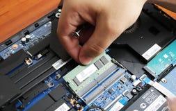 NIKOPOL, UCRÂNIA - EM JUNHO DE 2018: A posse do técnico a chave de fenda para reparar o computador, o conceito do material inform fotos de stock