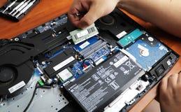 NIKOPOL, UCRÂNIA - EM JUNHO DE 2018: A posse do técnico a chave de fenda para reparar o computador, o conceito do material inform imagens de stock