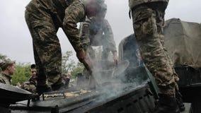 NIKOPOL UKRAINA, MAJ, -, 9, 2019: Ukraiński wojskowy gotuje żołnierz owsiankę i fund ludzi ono przy paradą na cześć Vic zbiory