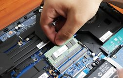 NIKOPOL, UKRAINE - JUNE, 2018: The technician hold the screwdriver for repairing the computer, the concept of computer hardware,. Repairing, upgrade and stock photos