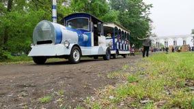 NIKOPOL, UKRAINE - MAI 2019: Der Zug der Kinder rollt die Kinder im Park folgende Eltern machen Fotos ihrer Kinder stock video