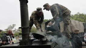 NIKOPOL, UKRAINE - MAY, 9, 2019: Ukrainian military cooks soldiers` porridge and treats people to it at the parade in honor of Vic. Ukrainian military cooks stock footage