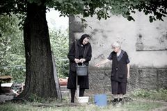People Balkan LifeStyle, Montenegro. NIKSIC, MONTENEGRO - JULY 25, 2016: two old women in black dresses are filling some buckets with the water of a faucet royalty free stock image