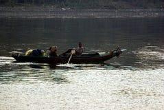 Nil rzeka blisko Aswnm, Egipt, Luty 21, 2017: Egipski rybak odtransportowywa dwa ludzie w ich łodzi po środku Ni Zdjęcie Stock