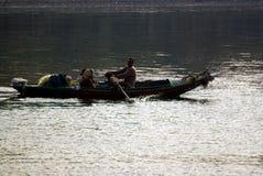Nil rzeka blisko Aswnm, Egipt, Luty 21, 2017: Egipski rybak odtransportowywa dwa ludzie w ich łodzi po środku Ni Zdjęcia Royalty Free