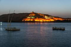 Nile Aswan and the West Bank with Tombs Old Kingdom Qubbet el-Hawa - `Dome of the Winds` at the crest of the hill. Nile Aswan and the West Bank with Tombs of the stock photography