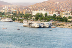 Nile River by Aswan City skyline with Boats. ASWAN, EGYPT - APRIL 26, 2014: Aswan city skyline with Nile river and Boats on April 26, 2014 in Aswan, Egypt Royalty Free Stock Images