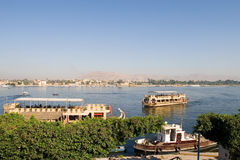 Nile River and boats in Luxor city  (Egypt). Immediately opposite, across the River Nile, lie the monuments, temples and tombs of the West Bank Necropolis, which Royalty Free Stock Photos