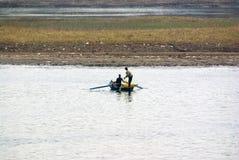 Nile River, dichtbij Aswnm, Egypte, 21 Februari, 2017: Twee vissers die in een kleine boot op Nile River vissen, één van hen die  Stock Foto