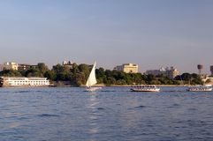 Nile river, Luxor Egypt. Boats sailing on river Nile with city in background, Luxor, Egypt Stock Photo
