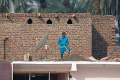 Nile River, nahe Aswnm, Ägypten, am 21. Februar 2017: Ägyptische Arbeitskraft, die ein Dach mit Steinen und Sand, nahe bei einem  Stockfoto