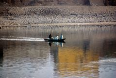 Nile River, near Aswan, Egypt. February 21, 2017: Two Muslim men and women dressed in djellaba crossing the Nile river in a small Royalty Free Stock Photo