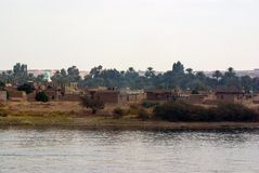 Nile river, near Aswan, February 16, 2017: Poor settlement of sand, brick and adobe located on the river bank and in the suburbs o. F the town of Aswan Stock Photos