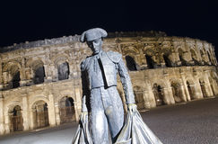 Nimes Arena at night. With statue of bullfighter Stock Photos